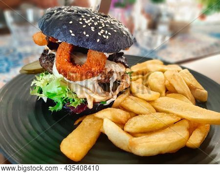 Cheeseburger with chips and onion rings on the plate