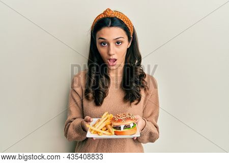 Young hispanic woman eating a tasty classic burger in shock face, looking skeptical and sarcastic, surprised with open mouth