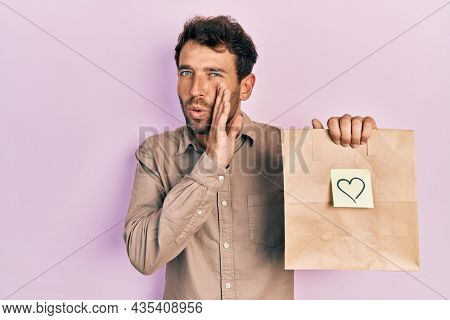 Handsome man with beard holding delivery paper bag with heart reminder hand on mouth telling secret rumor, whispering malicious talk conversation
