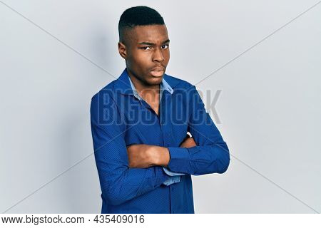 Young african american man with arms crossed gesture in shock face, looking skeptical and sarcastic, surprised with open mouth
