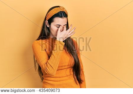 Young brunette teenager wearing casual yellow sweater tired rubbing nose and eyes feeling fatigue and headache. stress and frustration concept.