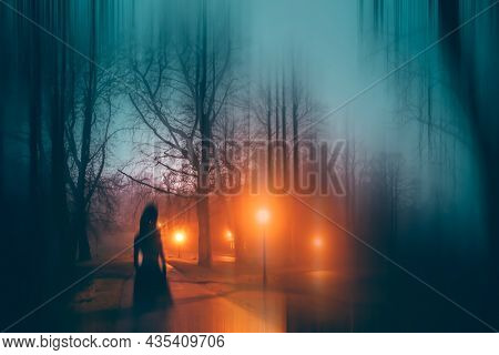 Horror background of a ghostly figure in enchanted a forest on a moody, foggy night. Halloween concept