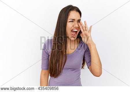 Young brunette woman standing by isolated background shouting and screaming loud to side with hand on mouth. communication concept.