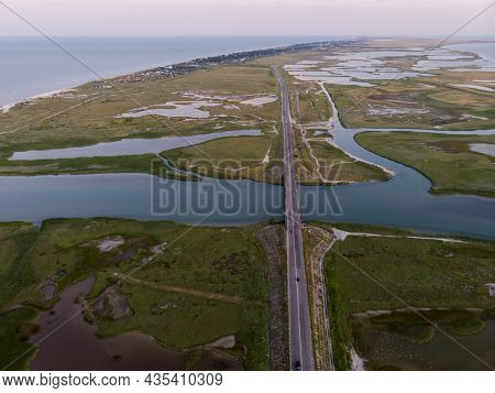 Aerial Drone View Of A Swamp At Amazing Bright Sunset. Aspalt Road Through The Lakes And Marsh