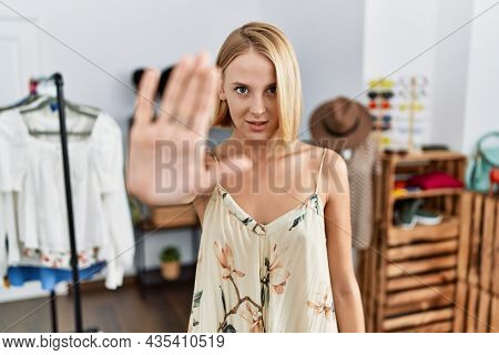Young caucasian woman at retail shop doing stop sing with palm of the hand. warning expression with negative and serious gesture on the face.