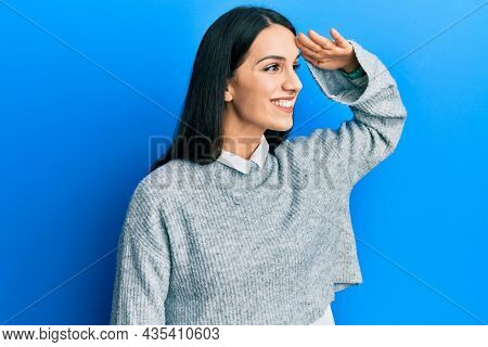 Young hispanic woman wearing casual clothes very happy and smiling looking far away with hand over head. searching concept.