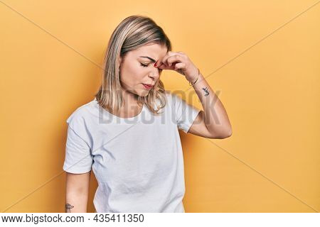 Beautiful caucasian woman wearing casual white t shirt tired rubbing nose and eyes feeling fatigue and headache. stress and frustration concept.