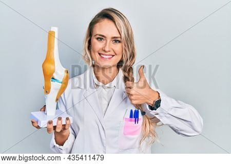 Beautiful young blonde doctor woman holding anatomical model of knee joint smiling happy and positive, thumb up doing excellent and approval sign