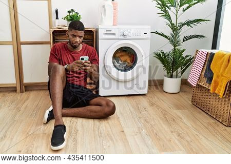 Young african american man using smartphone waiting for washing machine depressed and worry for distress, crying angry and afraid. sad expression.