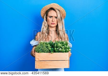 Beautiful young blonde woman holding wooden plant pot skeptic and nervous, frowning upset because of problem. negative person.
