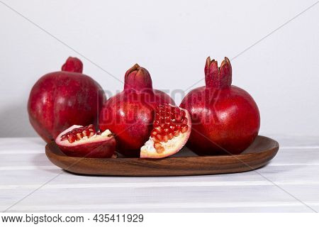 Ripe Pomegranates On Wooden Plate With On White Background, Red Fresh Fruits, Raising Hemoglobin