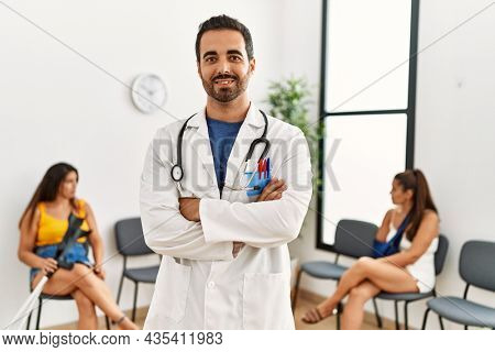 Young hispanic doctor smiling happy with arms crossed gesture. Standing at medical clinic waiting room with patients.