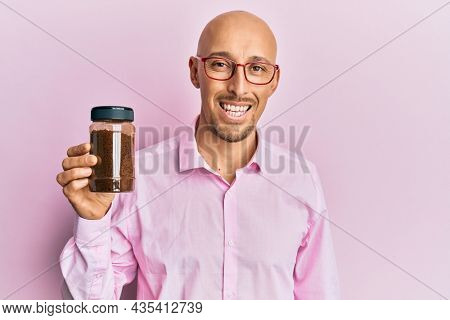 Bald man with beard holding soluble coffee looking positive and happy standing and smiling with a confident smile showing teeth