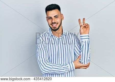 Young hispanic man with beard wearing casual striped shirt smiling with happy face winking at the camera doing victory sign. number two.