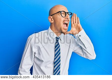 Bald man with beard wearing business clothes and glasses shouting and screaming loud to side with hand on mouth. communication concept.