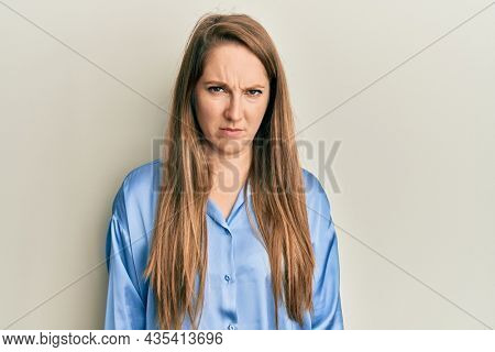 Young blonde woman wearing casual blue shirt skeptic and nervous, frowning upset because of problem. negative person.