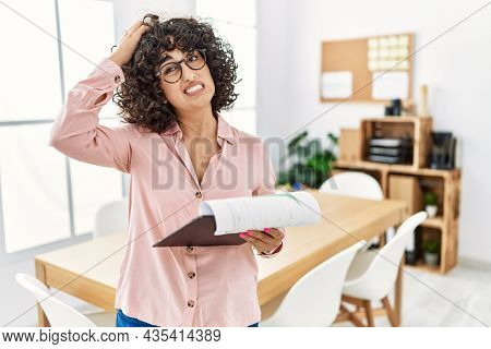 Young middle eastern woman wearing business style at office confuse and wondering about question. uncertain with doubt, thinking with hand on head. pensive concept.