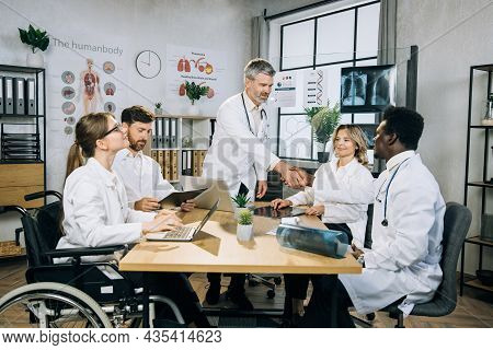Bearded Caucasian Doctor Shaking Hands And Greeting His Multi Ethnic Colleagues During Medical Semin