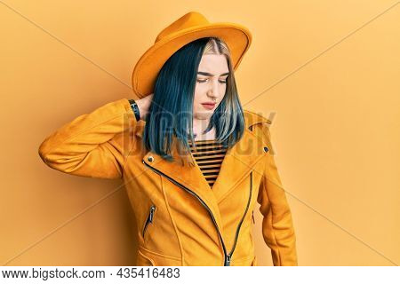 Young modern girl wearing yellow hat and leather jacket suffering of neck ache injury, touching neck with hand, muscular pain