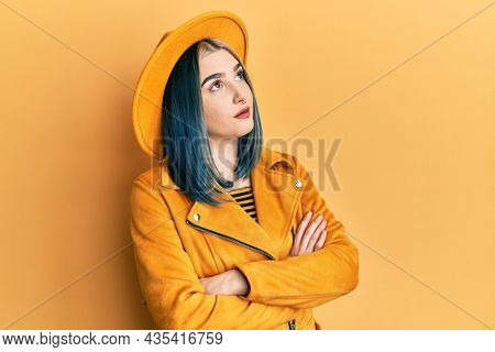 Young modern girl wearing yellow hat and leather jacket looking to the side with arms crossed convinced and confident