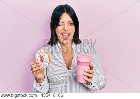 Young hispanic woman eating doughnut and drinking coffee winking looking at the camera with sexy expression, cheerful and happy face.