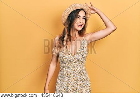 Young hispanic girl wearing summer hat very happy and smiling looking far away with hand over head. searching concept.