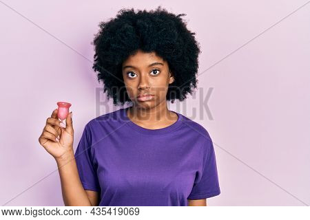 Young african american woman holding menstrual cup thinking attitude and sober expression looking self confident