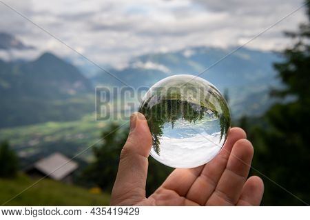 Hand Holding Glass Sphere In Front Of Valley, Cloudy Day In Summer, Alps In East Tyrol (austria)
