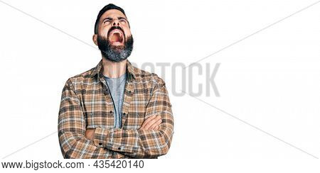 Hispanic man with beard with arms crossed gesture angry and mad screaming frustrated and furious, shouting with anger looking up.