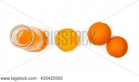 Top View Of A Ripe Oranges, Glass Bottle And Mug With Fresh Squeezed Orange Juice On White Backgroun