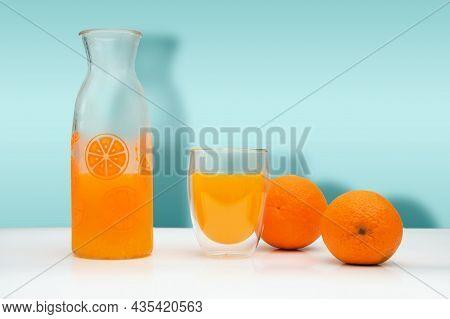 Ripe Oranges, A Glass Bottle And Mug With F Fresh Squeezed Orange Juice On White Background.