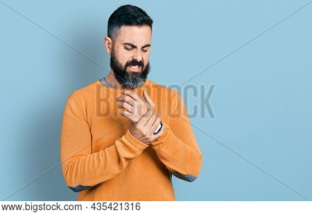 Hispanic man with beard wearing casual winter sweater suffering pain on hands and fingers, arthritis inflammation