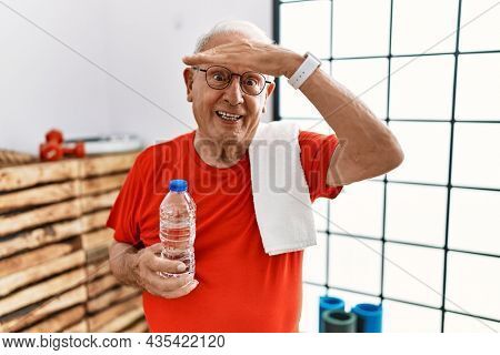 Senior man wearing sportswear and towel at the gym very happy and smiling looking far away with hand over head. searching concept.