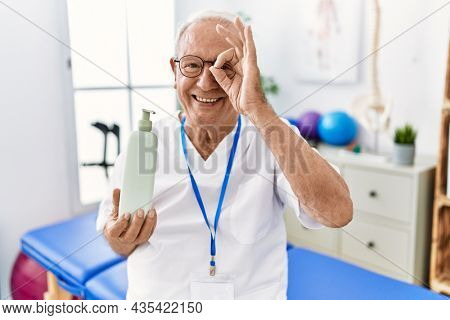 Senior physiotherapy man holding massage body lotion smiling happy doing ok sign with hand on eye looking through fingers