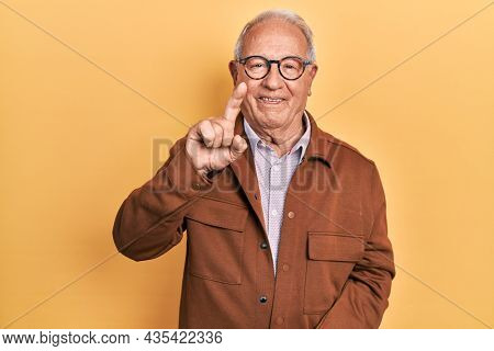 Senior man with grey hair wearing casual jacket and glasses showing and pointing up with finger number one while smiling confident and happy.