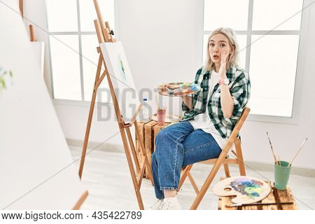 Young artist woman painting on canvas at art studio hand on mouth telling secret rumor, whispering malicious talk conversation