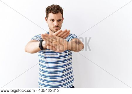 Handsome young man standing over isolated background rejection expression crossing arms and palms doing negative sign, angry face