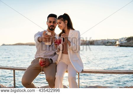 Loving Ethnic Couple Sitting On Embankment With Glasses Of Refreshing Summer Cocktails And Taking Se