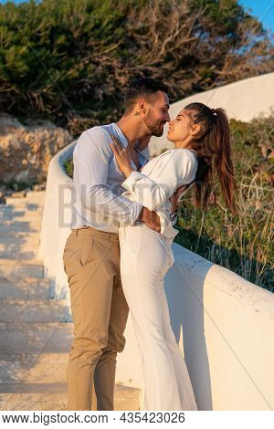 Side View Of Content Stylish Ethnic Couple Hugging And Touching Noses While Standing On White Stairs