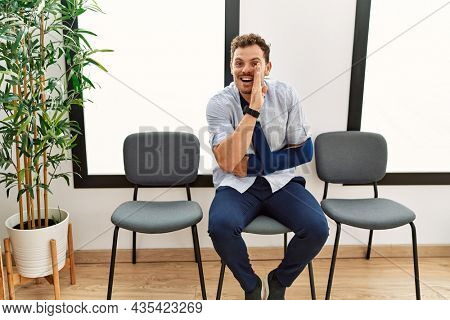 Handsome young man sitting at doctor waiting room with arm injury hand on mouth telling secret rumor, whispering malicious talk conversation
