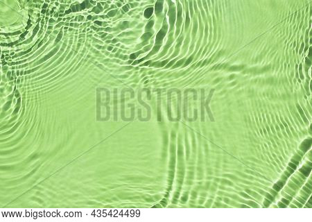 Water Spills On A Mint Green Background. Natural Sunlight And Shade. Beautiful Bursts And Glare. Sum