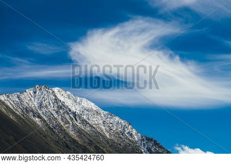 Scenic Sunny Landscape With High Snowy Mountain Top Under Cirrus Clouds In Blue Sky. Beautiful Alpin