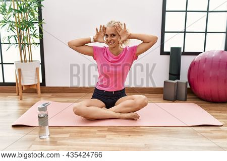 Middle age blonde woman sitting on yoga mat smiling cheerful playing peek a boo with hands showing face. surprised and exited