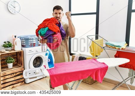 Young handsome man holding laundry ready to iron annoyed and frustrated shouting with anger, yelling with anger and hand raised