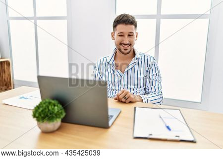 Young handsome man with beard working at the office using computer laptop winking looking at the camera with sexy expression, cheerful and happy face.