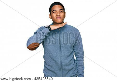 Young handsome hispanic man wearing casual sweatshirt cutting throat with hand as knife, threaten aggression with furious violence