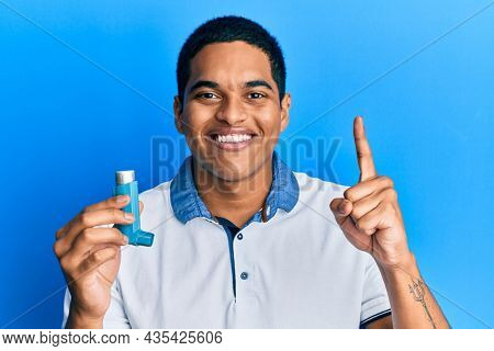 Young handsome hispanic man holding medical asthma inhaler smiling with an idea or question pointing finger with happy face, number one