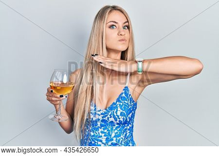 Young beautiful caucasian woman drinking a glass of white wine cutting throat with hand as knife, threaten aggression with furious violence
