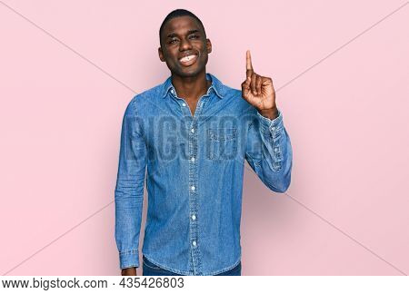 Young african american man wearing casual clothes showing and pointing up with finger number one while smiling confident and happy.