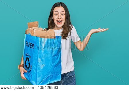 Young beautiful woman holding recycling wastebasket with paper and cardboard celebrating victory with happy smile and winner expression with raised hands
